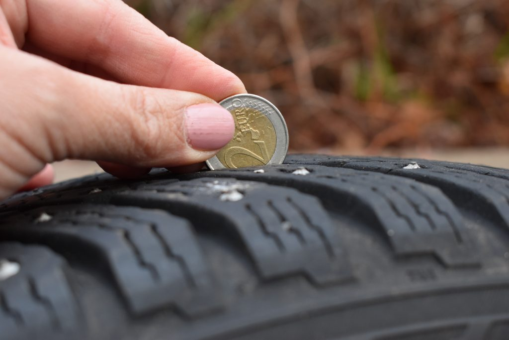 Checking tire thread depth with a two-euro coin