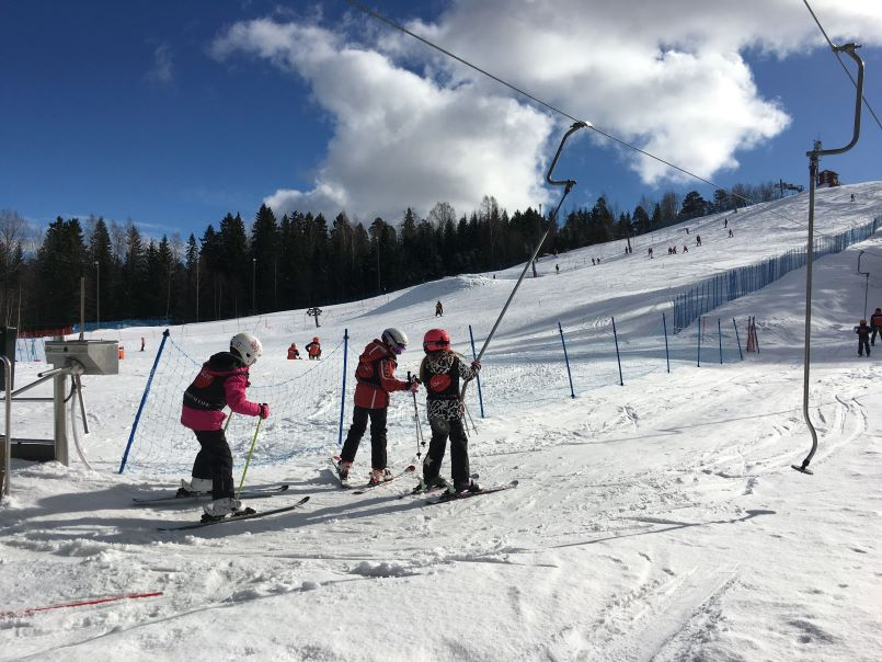 Children going up on a ski lift at a downhill skiing center in Finland.